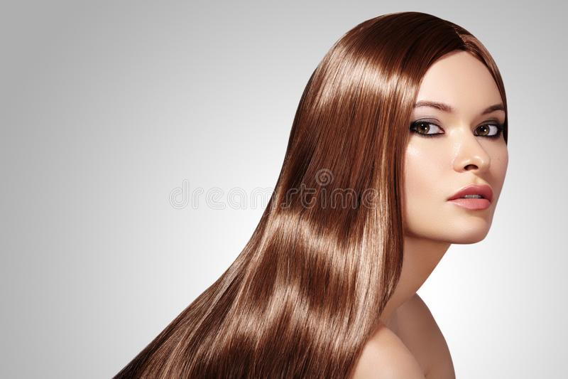 有长期平直的棕色头发的美丽的yong妇女 与光滑的光泽发型的性感的时装模特儿 与构成的秀丽 免版税库存图片