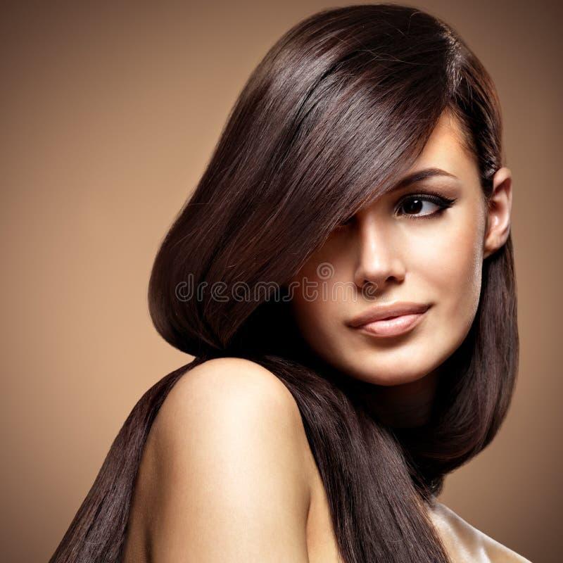 有长期平直的棕色头发的美丽的少妇 免版税图库摄影