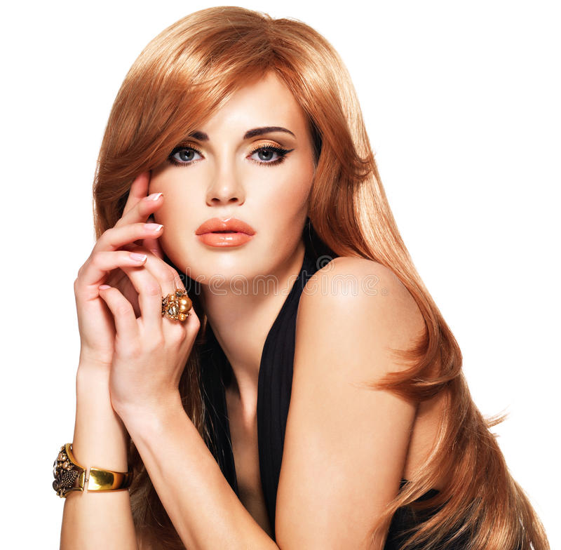 有长期平直的红色头发的美丽的妇女在一件黑礼服。 免版税图库摄影