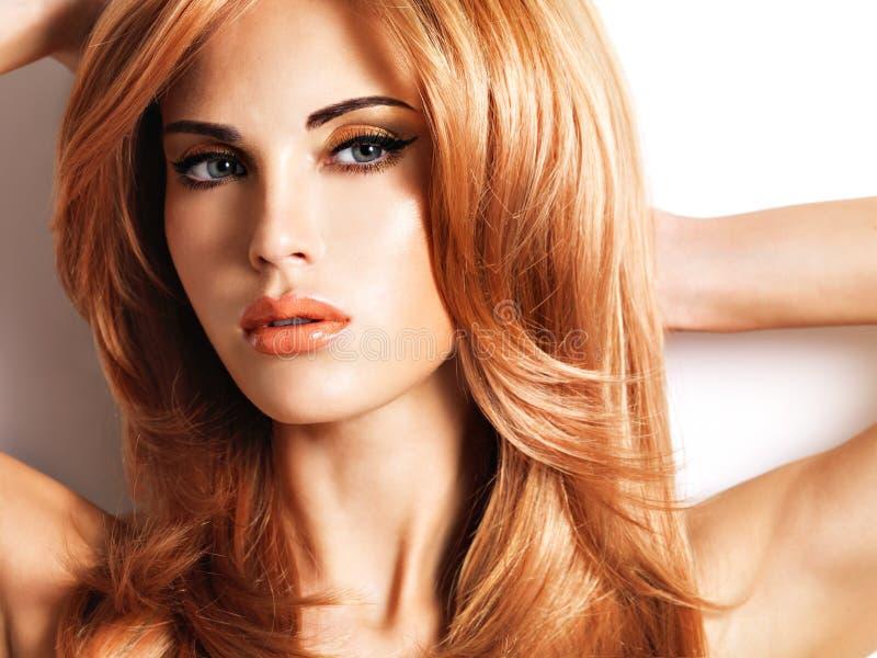 有长期平直的红色头发的美丽的妇女 免版税库存照片