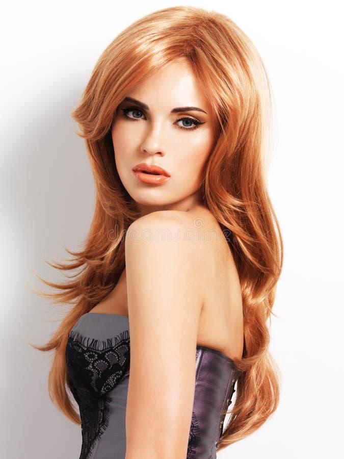 有长期平直的红色头发的美丽的妇女 库存照片