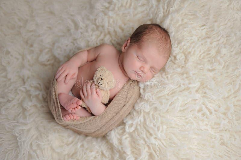 有长毛绒熊玩具的新出生的男婴 免版税库存图片