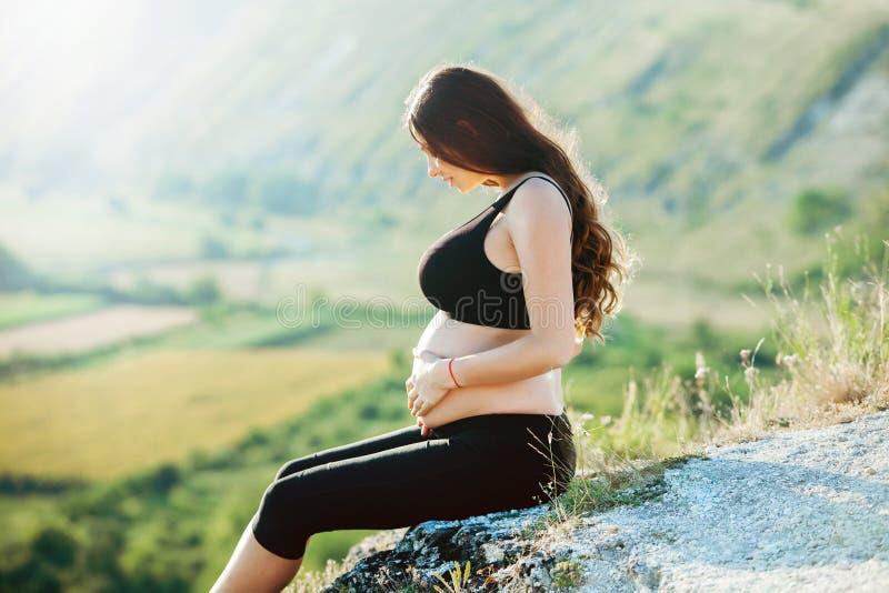 有长的健康头发和花的孕妇 等待婴孩的美女 未来母亲拥抱她的肚子 免版税库存图片