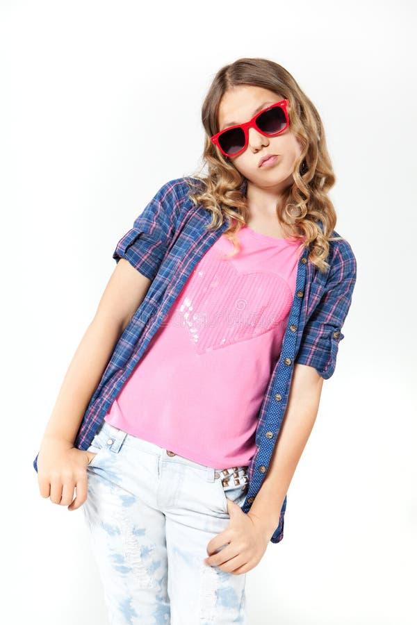 有长的卷发佩带的格子花呢上衣和牛仔裤的女孩 免版税库存图片