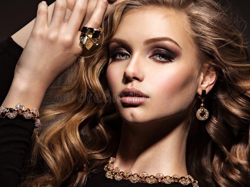 有长的卷发和金首饰的美丽的妇女 免版税图库摄影
