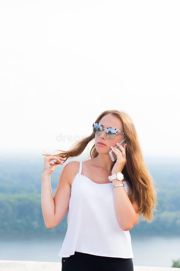有长的卷发的可爱的少妇,在太阳镜、白色上面和黑裤子谈话在电话 免版税库存照片