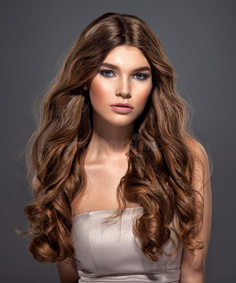 有长的卷发的性感和华美的棕色毛发的妇女 免版税图库摄影