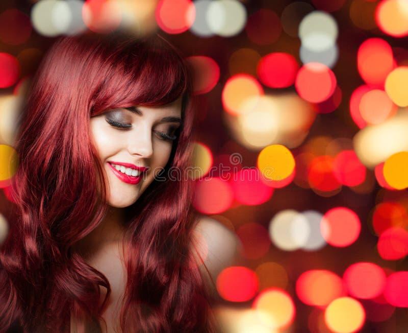 有长的卷发的红头发人妇女在明亮的颜色党bokeh 免版税库存图片