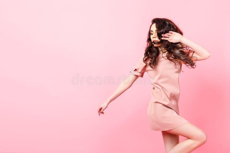 有长的卷发的美丽的时兴的女孩在一件桃红色礼服在桃红色背景的演播室 库存照片
