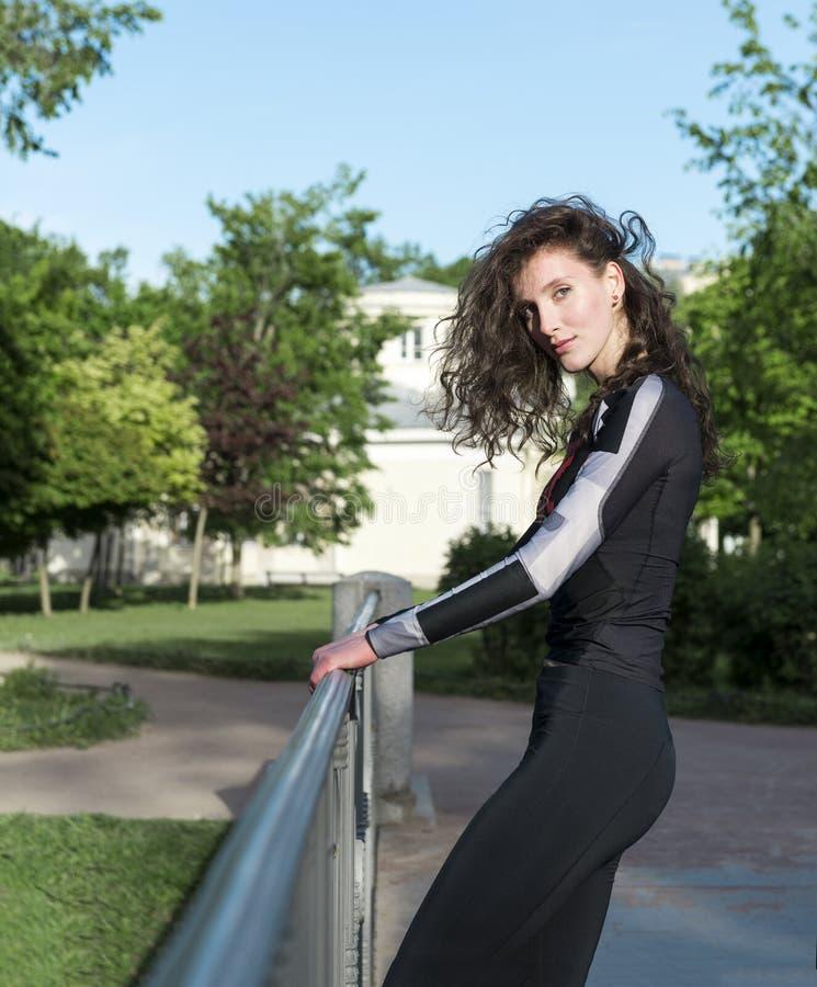 有长的卷发的1个白女孩在黑体育衣裳在美女的一张绿色背景画象的公园 免版税库存照片