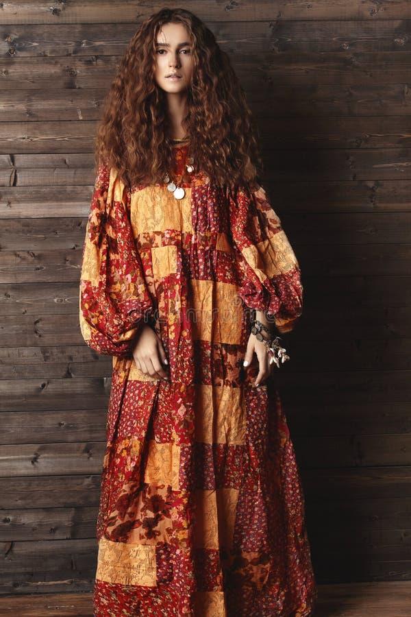 有长的卷曲发型的美丽的少妇,与深色的头发的时尚首饰 印地安样式衣裳,长的礼服 库存图片
