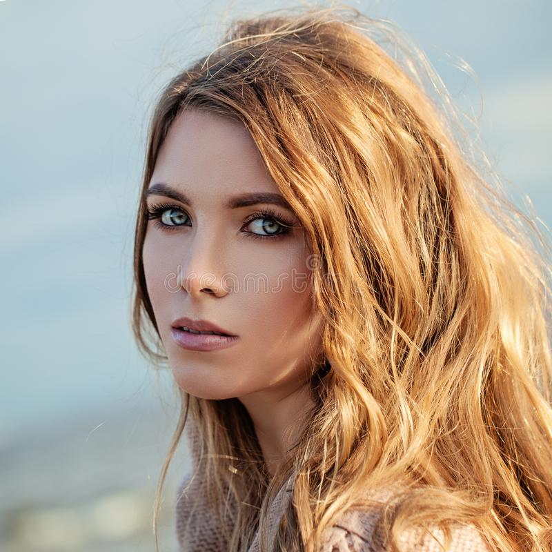 有长的卷曲妇女的好式样女孩有有风吹的头发的 库存照片