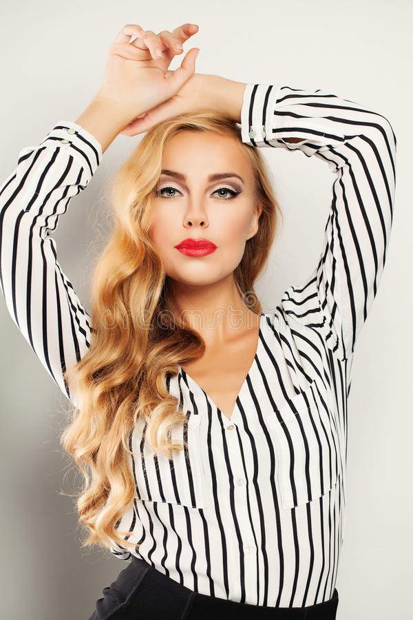 有长的卷曲白肤金发的发型的时兴的金发妇女 免版税图库摄影