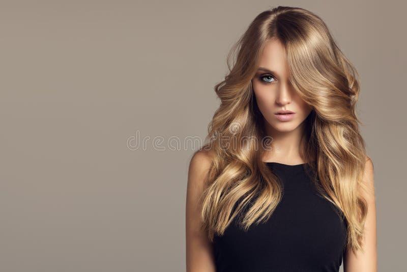 有长的卷曲美丽的头发的白肤金发的妇女 免版税图库摄影