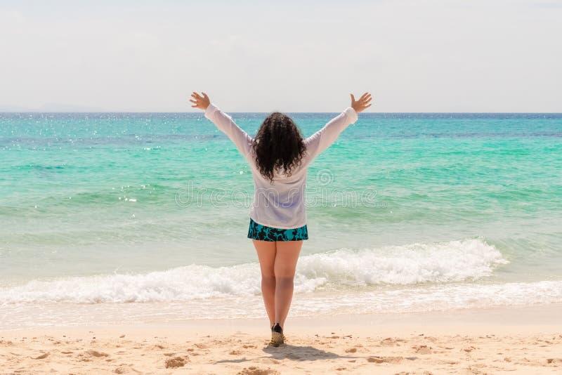 有长的卷曲黑色头发的一名年轻壮健妇女站立用她的手反对海 库存图片