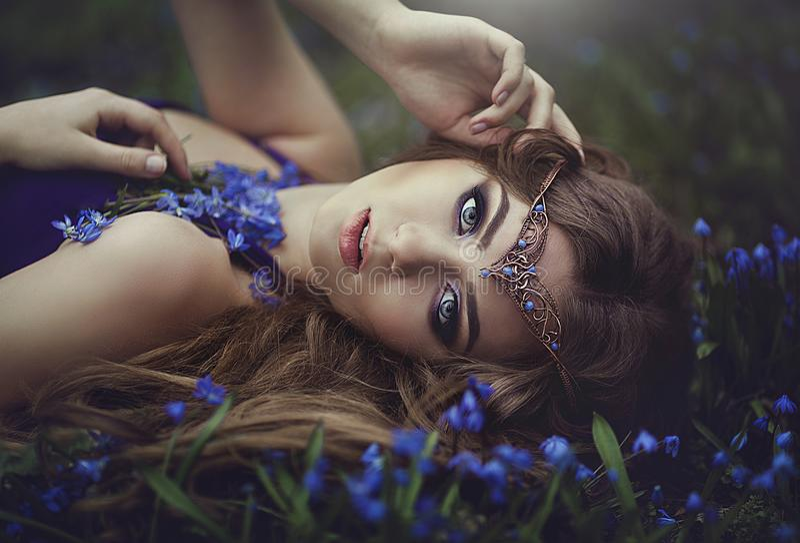 有长的头发和蓝眼睛的矮子女孩在冠状头饰在春天森林蓝色森林花休息 女孩公主梦想 免版税库存图片