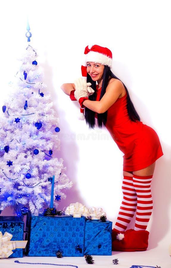 有长的头发在一套红色地精衣服和一个镶边盖帽的深色的女孩在用蓝色球装饰的一棵白色圣诞节树 免版税库存图片