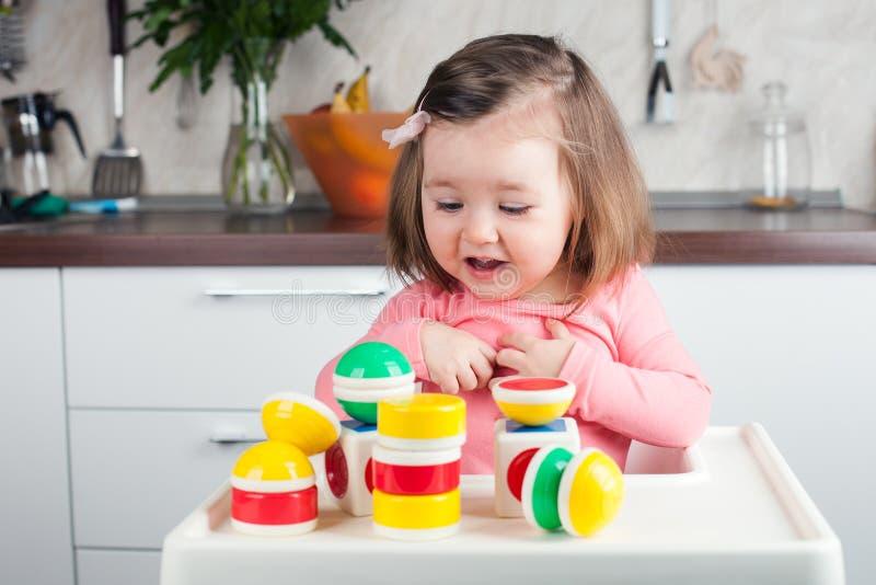 有长的头发的一个两岁的女孩在家使用与设计师,建造塔,高兴在成功的建筑 免版税库存照片