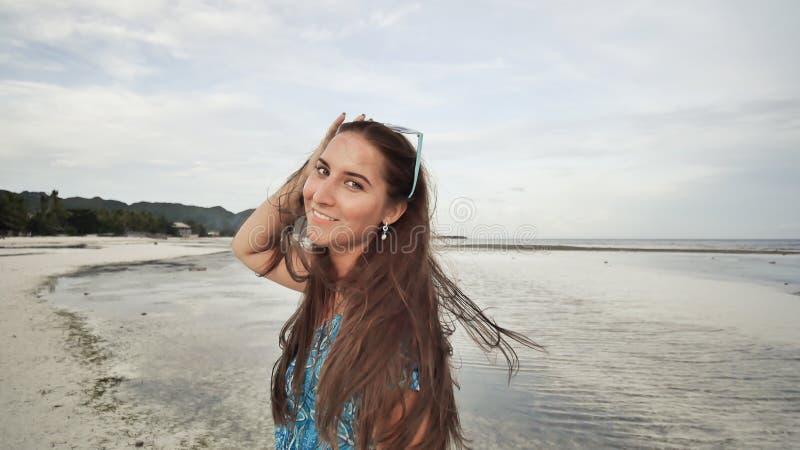 有长的头发的一个美丽的女孩在一件长的蓝色礼服沿海滩漫步 摆在异乎寻常的海岸的照相机的女孩 库存图片