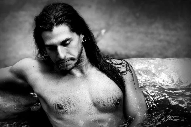 有长的头发的一个英俊的在瀑布的人和穿甲在雨林Tarzan概念 北京,中国黑白照片 免版税图库摄影