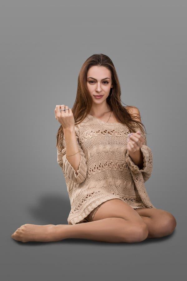 有长的头发的可爱的女孩在毛线衣和长袜赤足坐地板 免版税库存照片