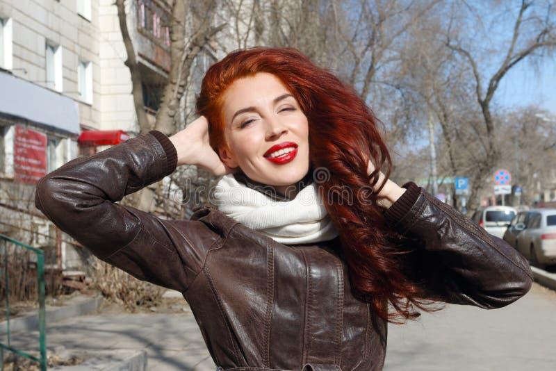 有长的头发的女孩在皮夹克微笑 免版税库存图片