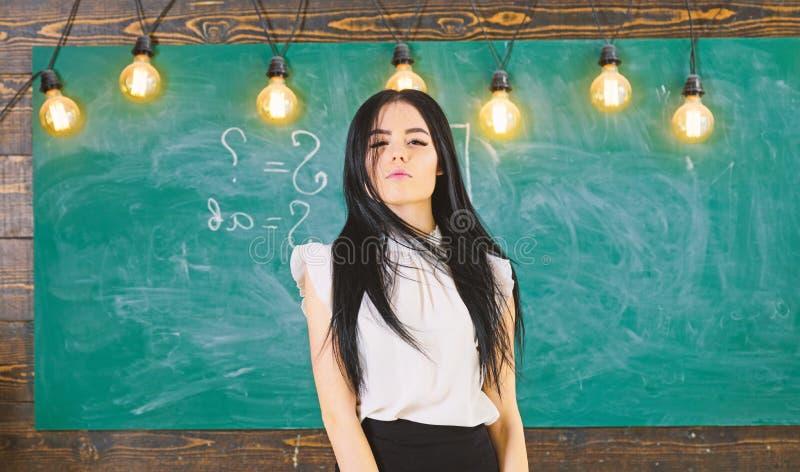 有长的头发的妇女在白色女衬衫在教室站立 准备好的老师开始教训,拷贝空间 精华学校 免版税库存照片