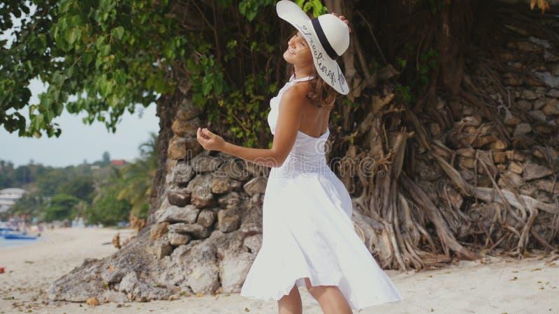 有长的头发的年轻深色的妇女在白色drees和帽子步行在热带海滩享用 免版税库存图片