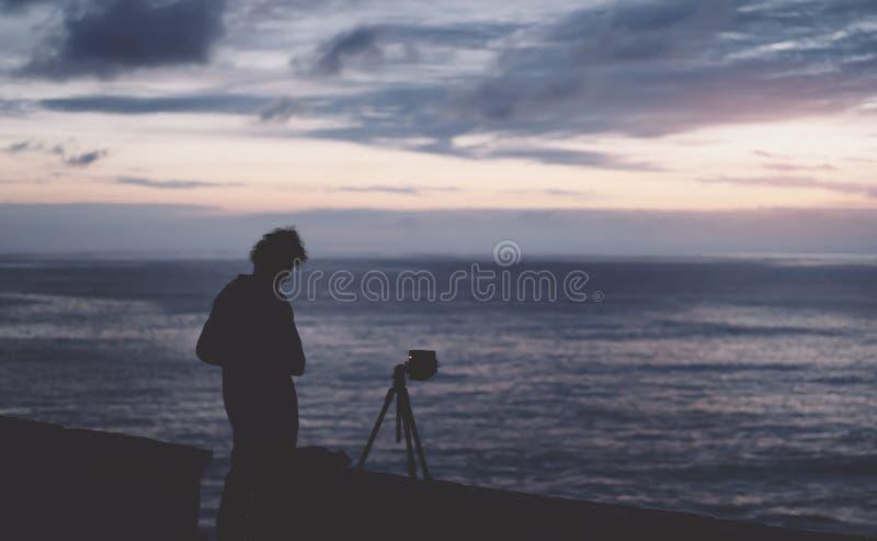 有长的头发的年轻行家人在日落背景的晚上,剪影摄影师拍在海日落的照片的一张照片 库存照片