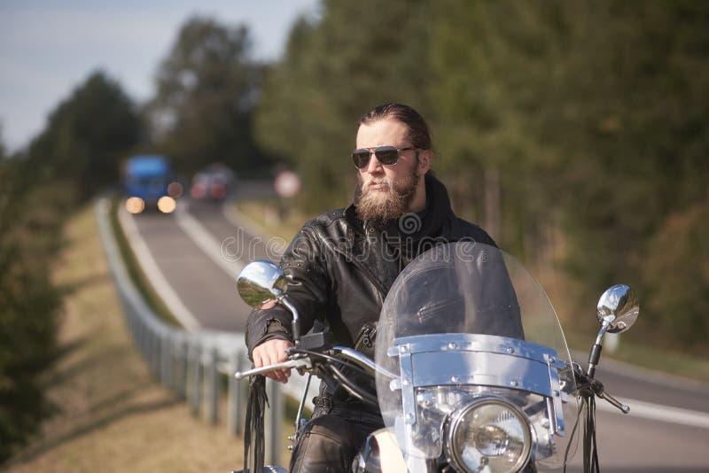 有长的头发的有胡子的骑自行车的人在黑皮夹克坐现代摩托车 免版税库存照片