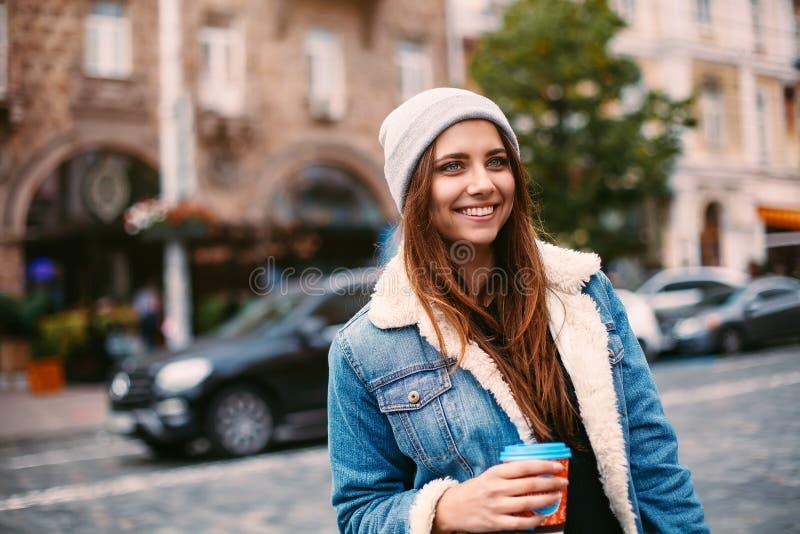 有长的头发的画象俏丽的女孩在牛仔布外套走在街道上的用咖啡去 她看起来激动对照相机 库存照片