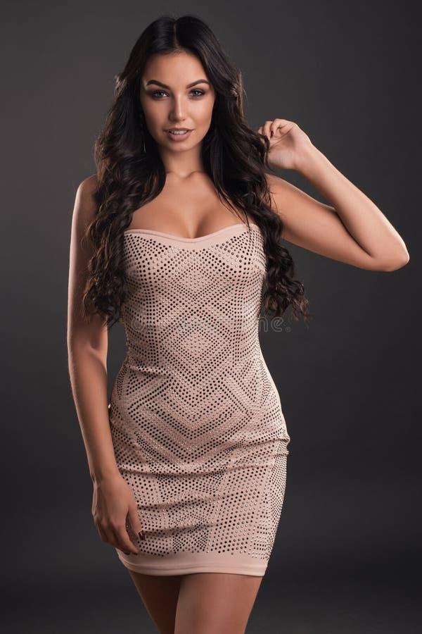 有长的头发的美丽的少妇在一件紧的发光的礼服 免版税库存图片