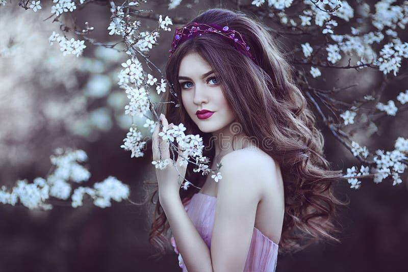 有长的头发的美丽的浪漫女孩在开花的树附近的桃红色礼服 库存照片
