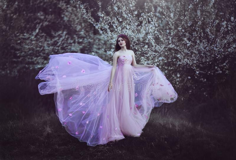 有长的头发的美丽的浪漫女孩在开花的树附近的桃红色礼服 免版税库存图片