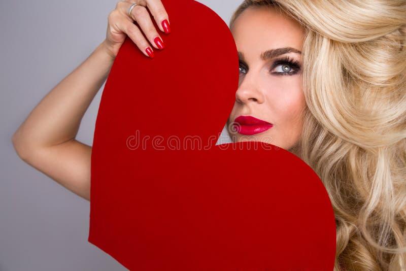 有长的头发的美丽的金发碧眼的女人,站立赤裸和用红色心脏盖 免版税库存图片