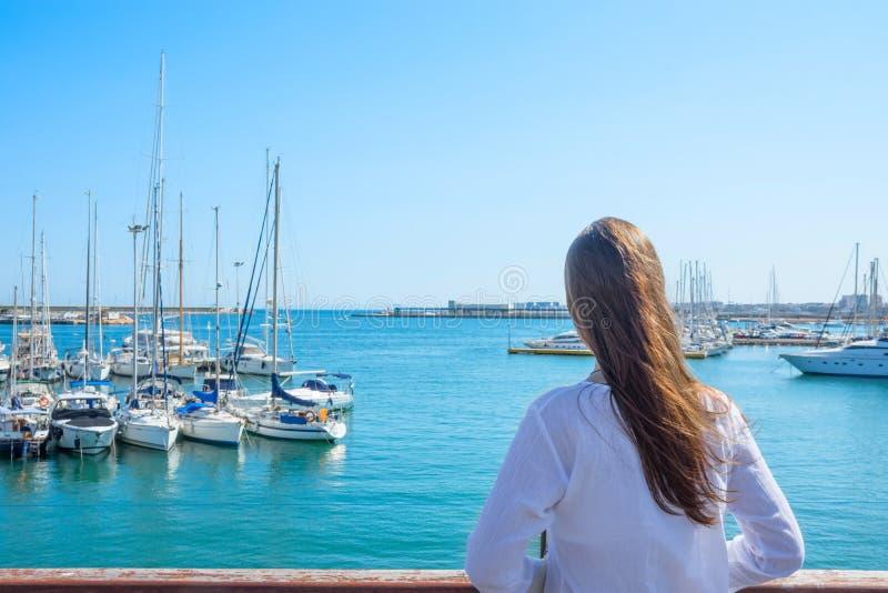 有长的头发Boho长袍立场的可爱的年轻白种人妇女在海滩看游艇在小游艇船坞停泊的帆船 海天空 免版税库存图片