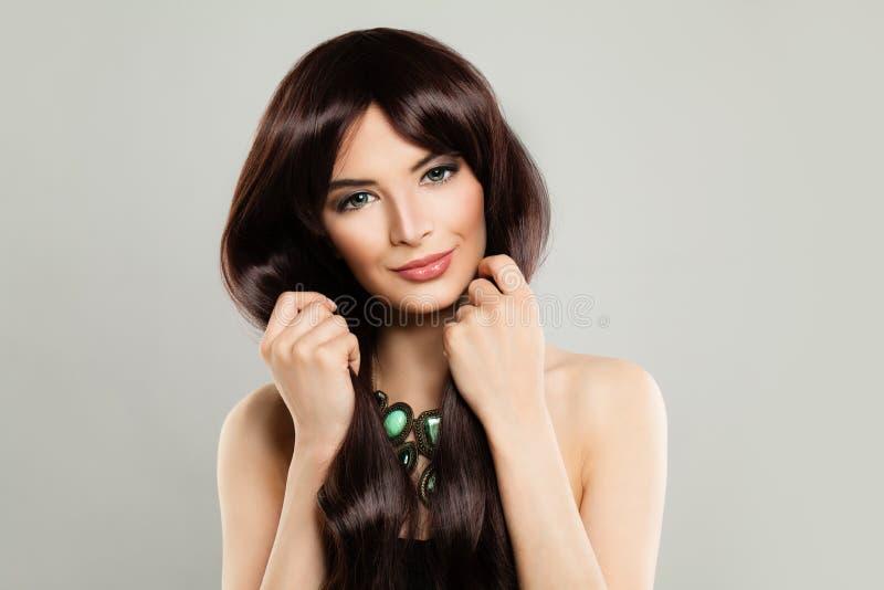 有长的布朗柔滑的头发的逗人喜爱的在背景的妇女和构成 免版税库存图片
