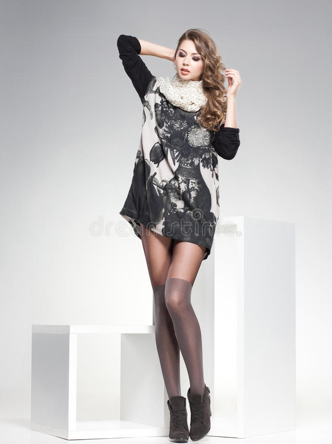 有长的性感的腿的美丽的妇女在演播室穿戴了典雅摆在 免版税库存照片