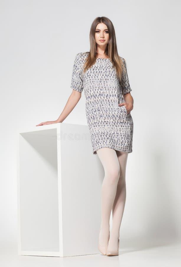 有长的性感的腿的美丽的妇女在演播室穿戴了典雅摆在 免版税库存图片
