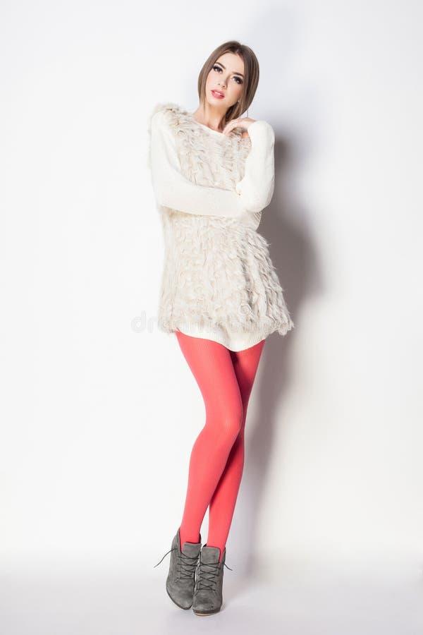 有长的性感的腿的美丽的妇女穿戴了典雅摆在 库存图片