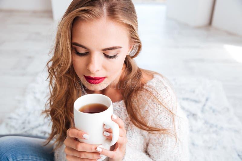 有长的拿着茶杯的头发和红色唇膏的妇女 免版税图库摄影