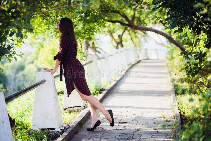 有长的有风头发的年轻俏丽的妇女在站立在台阶的紫罗兰色礼服 免版税图库摄影