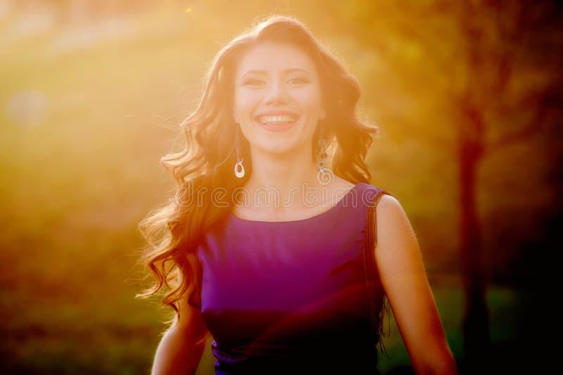 有长的有风头发的年轻俏丽的妇女在站立在绿草的典雅的紫罗兰色礼服 图库摄影