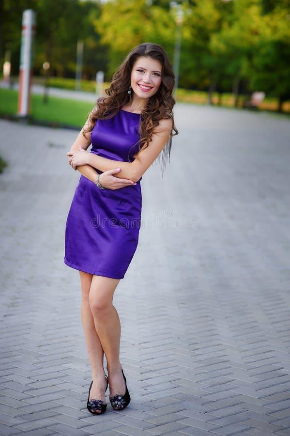 有长的有风头发的年轻俏丽的妇女在站立在绿草的典雅的紫罗兰色礼服 库存照片