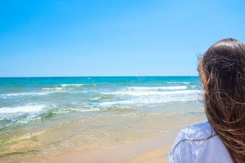 有长的栗子头发的年轻可爱的白种人妇女有回到在沙子海滩的观察者立场的看绿松石海天线 库存图片