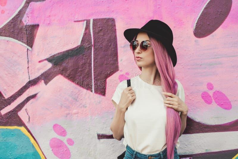 有长的桃红色头发、帽子和太阳镜的美丽的时髦的年轻行家妇女在街道上 免版税库存图片