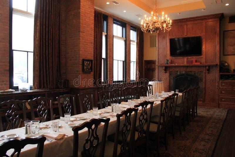 有长的桌、欢迎赞助人为参观,哈维的餐馆和酒吧的,萨拉托加,纽约温暖的木头和砖室, 2015年 免版税库存图片