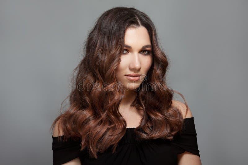 有长的棕色卷发的美女 免版税图库摄影