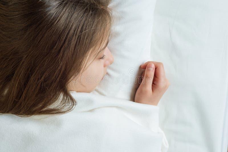 有长的棕色头发的女孩孩子睡觉在一个枕头的在床上 关闭女孩朝向,在白色床上 图库摄影