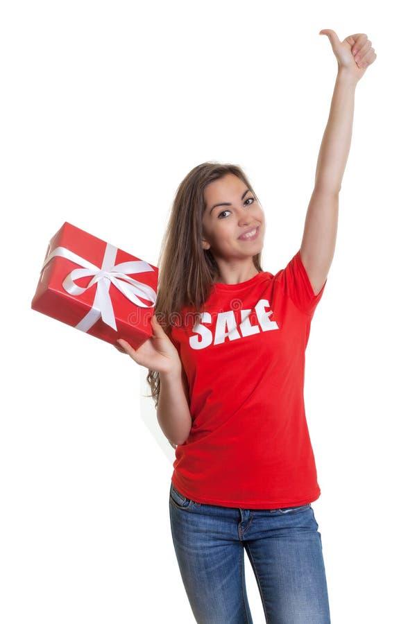 有长的棕色头发和礼物销售的愉快的妇女在衬衣 免版税库存图片